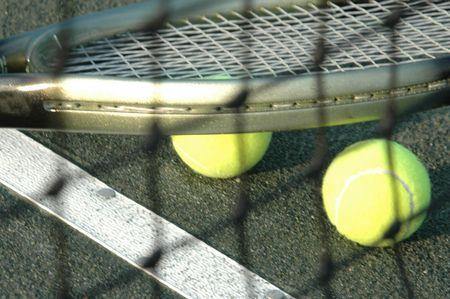 tennis racquet and balls through the net photo