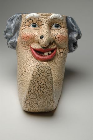 a scary ceramic face with a big mole on the nose and a very long chin