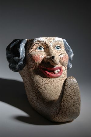 long nose: a scary ceramic face with a big mole on the nose and a very long chin with shadows Stock Photo