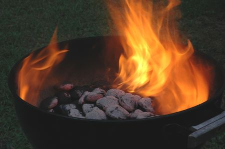 charcoals flaming hot in a kettle grill Stock Photo