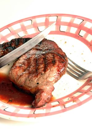 ribbed slab: a rib eye steak on a plate with natural  juices and a fork and knife Stock Photo