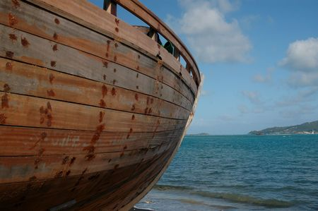 an almost completed hand made boat looking out to the sea and a caribbean island Stock Photo