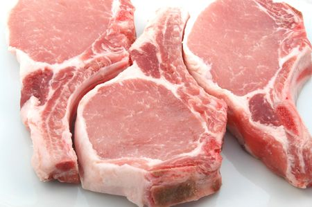 three plump center cut pork chops on white Stock Photo