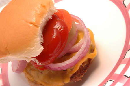 catsup: juicy cheeseburger on a bun with catsup onions and tomato slices Stock Photo
