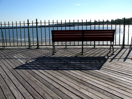 ruminate: bench with shadows on a boardwalk by the beach Stock Photo