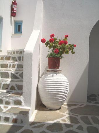 greek pot: grande vaso di ceramica con gerani in isole greche Archivio Fotografico