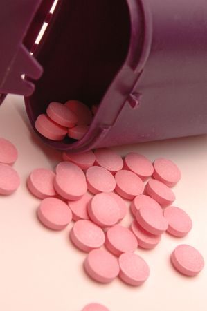 ingest: vitamin pills with focus on pills directly under body of the bottle to draw the eye in