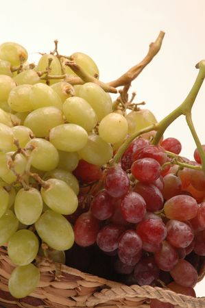 seedless: green and red seedless grapes in wicker basket on white background Stock Photo