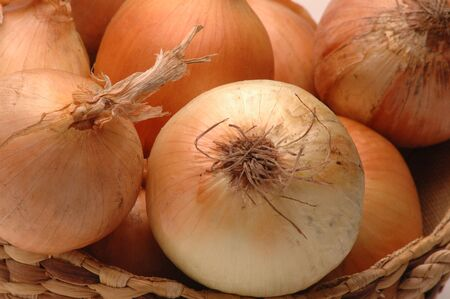 close up of onions in a basket: fresh yellow onions in wicker basket horizontal