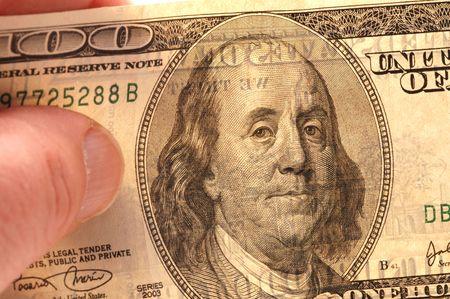 statesman: macro shot of hand holding 100 usa dollars with portrait ben franklin detail