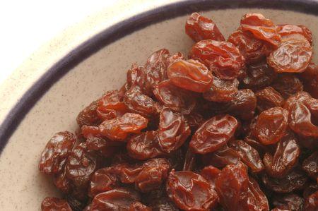earth tone:  raisins on earth tone bowl white background