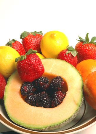half cantaloupe with colorful fruit and copy space photo
