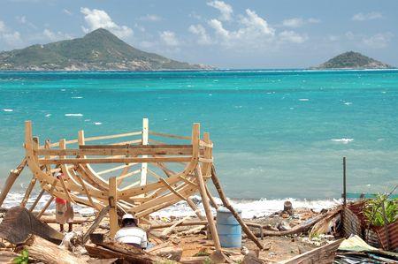 martinique: barco que se est� construyendo a mano con la Peque�a Martinica en el fondo