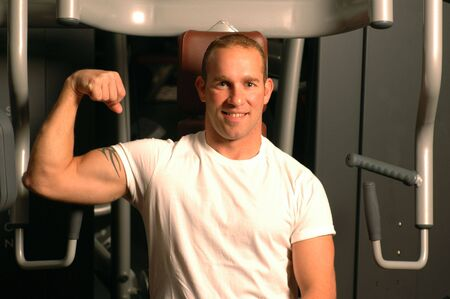 strong man flexing muscles in gym