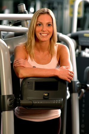 beautiful blond woman in gym with fitness equipment