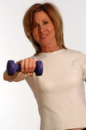 pretty fitness instructor with dumbbells SHOULDER RAISE photo