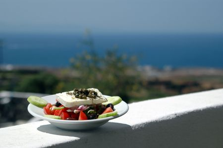 greek salad on a taverna wall with scenic view of the aegean sea