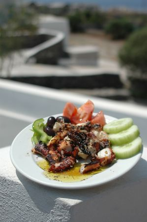 freshly grilled octopus with scenic background greek islands