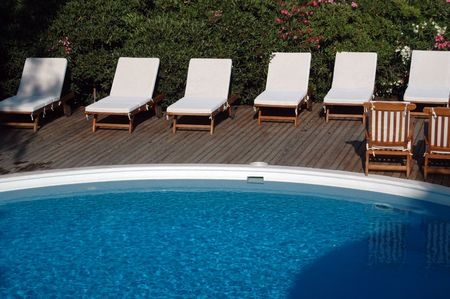 swimming pool with lounge chairs and flowering plants photo