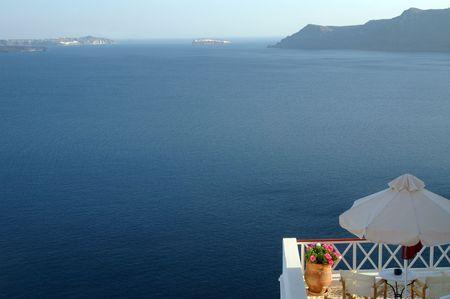 overlooking: el santorini florece por el caf� que pasa por alto las islas griegas del mar horizontales