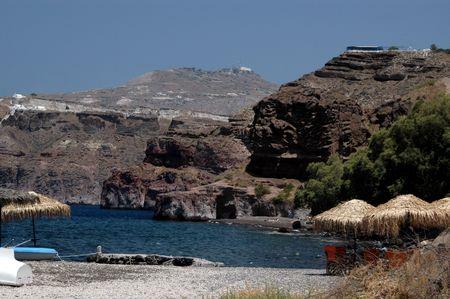 black sand beach under cliff caldera with taverna greek islands Stock Photo - 539771