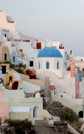 greek island church with classic blue dome surrounded by houses and hotels photo