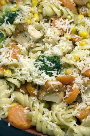 garlic chicken pasta sauce grilled broccoli corn carrots dinner with grated cheese photo