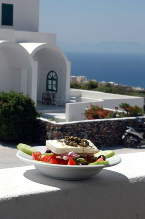 greek islands: greek salad with cycladic architecture in background over aegean sea