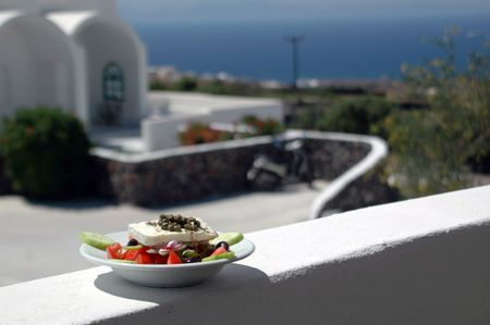 aegean: greek salad in sharp focus with cycladic architecture in background over aegean sea Stock Photo