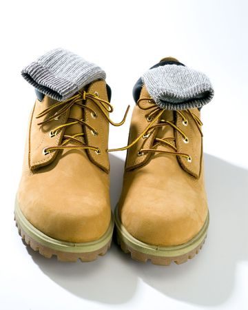 durable: rugged casual shoes in tan  suede on white background with warm socks Stock Photo