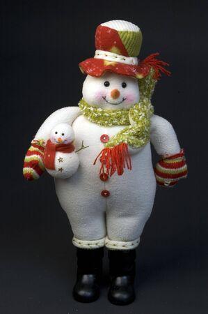 mujer hombre de nieve con un niño con gorro de lana y bufanda Foto de archivo - 566962