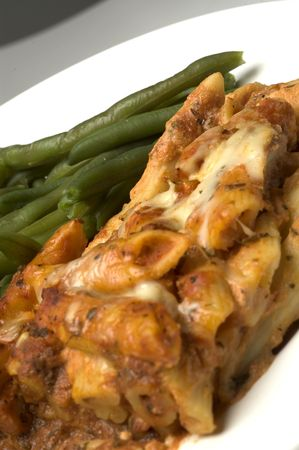 baked ziti with whole green beans dinner on white plate photo