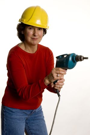 woman middle age: woman middle age with electric drill wearing safety helmet