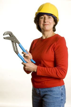 woman middle age: woman middle age with tool channel lock wrench plier wearing safety helmet Stock Photo