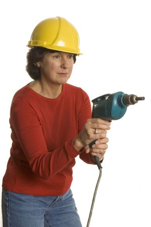 woman middle age: woman middle age with electric drill wearing safety helmet smiling