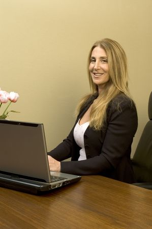 female executive at desk in office with computer and flowers