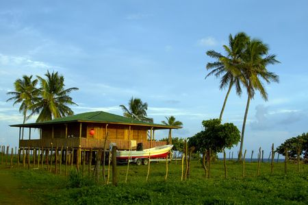 island house with large fishing boat and grass covered dirt road nicaragua