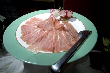 ham proscuitto on plate in restaurant sliced display Фото со стока