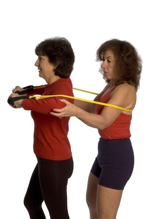 trainer and client exercising with stretch bands at the gym photo