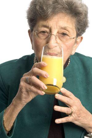 oj: ooh a nice glass of orange juice for a pretty woman senior Stock Photo