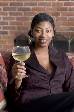 nosering: beautiful black woman toasting with wine on sofa with fireplace