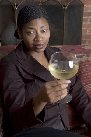 cornrows: beautiful black woman toasting with wine on sofa with fireplace