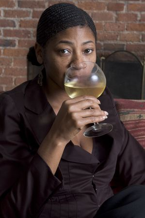 beautiful black woman toasting with wine on sofa with fireplace photo