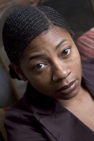 cornrows: mujer negra hermosa que sonr�e en el sof� Foto de archivo