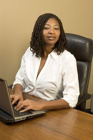 trenzas en el cabello: Negro atractiva mujer en la oficina de trabajo de ordenador de peinados