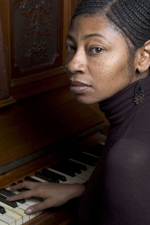 nosering: pretty black woman at piano with braided hair and nose ring