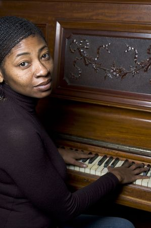 pretty black woman at piano with braided hair and nose ring photo
