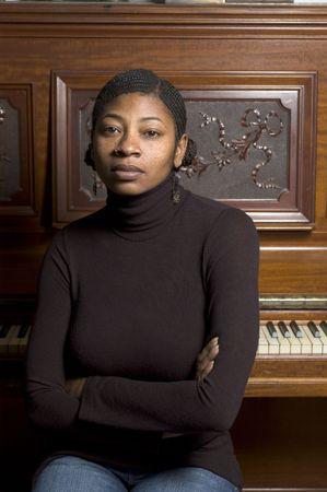 trenzas en el cabello: la mujer negra bonita en el piano con el pelo trenzado y la nariz suenan