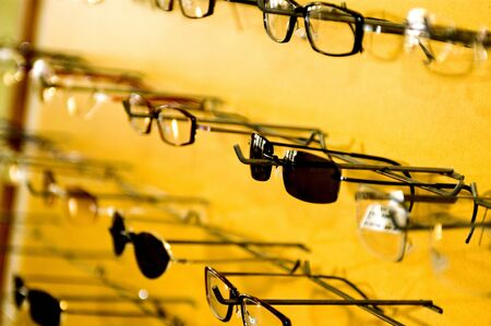 display of eyeglass frames on a store wall focus on sunglasses shallow depth of field photo