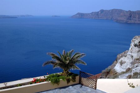 santorini flowers by cafe overlooking the sea greek islands with sailboat photo